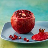 A pomegranate and red seeds of fruit on a blue plate. royalty free stock images