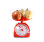 Pomegranate on red weighing scale Royalty Free Stock Photos