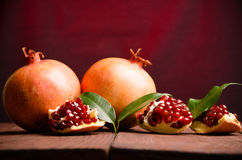the pomegranate is ripe. cut into pieces of ripe pomegranate. on wooden boards. Royalty Free Stock Images