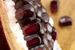 Pomegranate. Ripe pomegranate seeds on wooden background Stock Photography