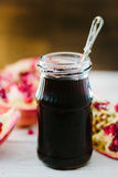 Pomegranate sauce on glass bottle surrounded by pomegranate halves. Pomegranate sauce on glass bottle surrounded by pomegranate halves stock photos
