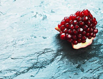 Pomegranate section on wet turquoise stone. Stock Photos