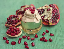 Pomegranate seed oil in bottle on blue wooden background Royalty Free Stock Photography