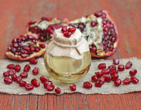 Pomegranate seed oil in bottle on red wooden background Stock Images