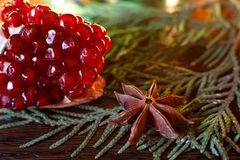 Pomegranate seeds and anise on a wooden table with colorful backlight. selective focus. Background for new year greeting card royalty free stock image