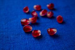 Pomegranate seeds upon blue linen Stock Photography