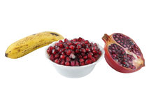 Pomegranate Seeds in a Bowl. Bowl full of Pomegranate seeds with a half-portion of the fruit and a banana in the background Stock Photography