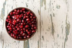 Pomegranate seeds in a bowl on a old wooden background.  royalty free stock photography