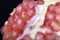 Pomegranate. Seeds closeup on the black ground Royalty Free Stock Photos