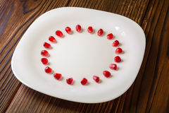 Pomegranate seeds in form of circle on white plate on rustic woo Stock Photography