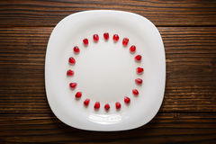 Pomegranate seeds in form of circle on white plate stock images