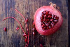 Pomegranate seeds in the form of heart on a wooden Stock Photography