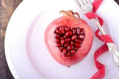 Pomegranate seeds in the form of heart on a wooden Royalty Free Stock Photos