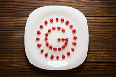 Pomegranate seeds in form of letter G on white plate on rustic w stock images