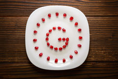 Pomegranate seeds in form of letter G on white plate Stock Image