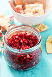 Pomegranate seeds in jar with membrane and skin in bowl left in the background. On blue surface Stock Images