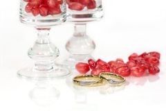 Pomegranate seeds and marriage rings Stock Photography