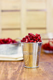 Pomegranate seeds  in a metal bucket on the wooden background Royalty Free Stock Photos