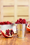 Pomegranate seeds in a metal bucket on the wooden background Royalty Free Stock Photography
