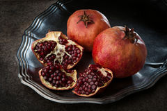 Pomegranate with seeds on the metal plate. Ripe juicy pomegranate with seeds on the metal plate Royalty Free Stock Images