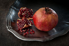Pomegranate with seeds. Ripe juicy pomegranate with seeds on the metal plate Royalty Free Stock Photo