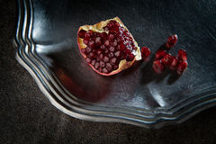 Pomegranate seeds. Ripe juicy pomegranate seeds on a metal plate Royalty Free Stock Photo