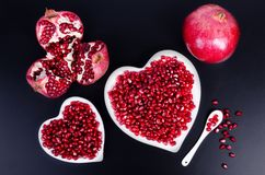 Pomegranate seeds in a shape of a heart on wooden background. stock photos