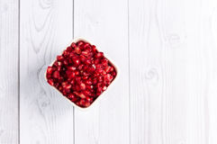 Pomegranate seeds in the square bowl on the white wooden table Royalty Free Stock Image