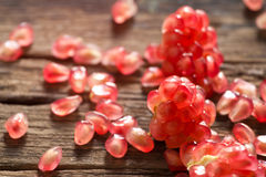 Pomegranate seeds vibrant on a wooden background Stock Images