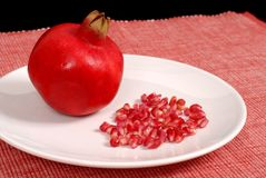Pomegranate and seeds on white plate. Whole pomegranate with seeds on white plate Royalty Free Stock Photo