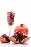 Pomegranate seeds and a whole pomegranate. A pomegranate broken open, full of ripe, red seeds. Pomegranate seeds in a long-stemmed glass and an entire Punica Royalty Free Stock Photo