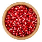 Pomegranate seeds in wooden bowl isolated on white royalty free stock photos