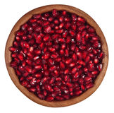 Pomegranate seeds in a wooden bowl on a white Royalty Free Stock Images