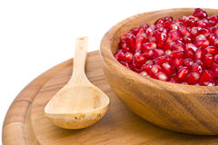 Pomegranate seeds and wooden utensils. On white background Stock Images