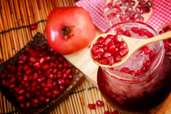 Pomegranate Set. Good healthy by Pomegranate seed on wooden spoon and cool Pomegranate juice set on red Themes tone background. Have some space for write royalty free stock photo