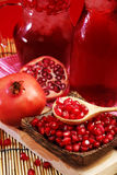 Pomegranate Set. Good healthy by Pomegranate seed on wooden spoon and cool Pomegranate juice set on red Themes tone background. Stock Photo