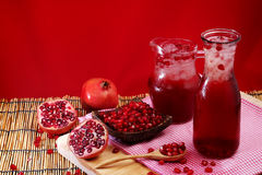 Pomegranate Set. Good healthy by Pomegranate seed on wooden spoon and cool Pomegranate juice set on red Themes tone background. Royalty Free Stock Images