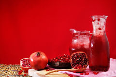 Pomegranate Set. Good healthy by Pomegranate seed on wooden spoon and cool Pomegranate juice set on red Themes tone background. Stock Images