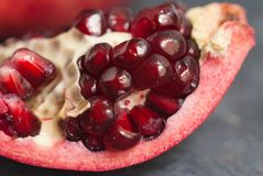 Pomegranate Slice Fruit. Close up Granate Seeds in slice. Macro image. vitamine and Healthy concept. Gray Textured Background. Pomegranate Slice Fruit. Close up Royalty Free Stock Photo