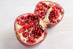 A pomegranate sliced in half. On a white wooden surface stock image