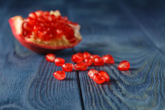 Pomegranate slices and garnet fruit seeds on table. Selective fo Royalty Free Stock Photos