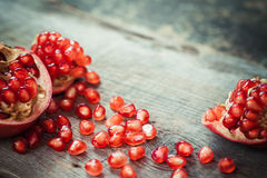 Pomegranate slices and garnet fruit seeds on table. Stock Photos