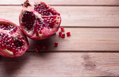 Pomegranate slices and garnet fruit seeds on table royalty free stock photos