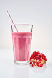 Pomegranate smoothie in tall glass next to fruit. With subtle reflection over gray background royalty free stock photography
