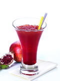 Pomegranate sorbet. A pomegranate sorbet in a glass with a whole and a halved pomegranate royalty free stock image