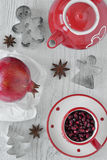 Pomegranate and star anise with tea set. Composition with pomegranate, star anise, tea set and cookie cutters Stock Photo