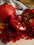 Pomegranate still. Two pomgranates, one split open showing berries and berries surrounding it Stock Photo