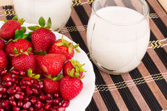 Pomegranate and strawberries with milk. Stock Photo