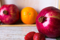 Pomegranate and strawberry. Pomegranate on a background fruit in a box Stock Image