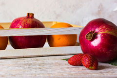 Pomegranate and strawberry on fruit background. Pomegranate fruit on a background in a box Stock Photo